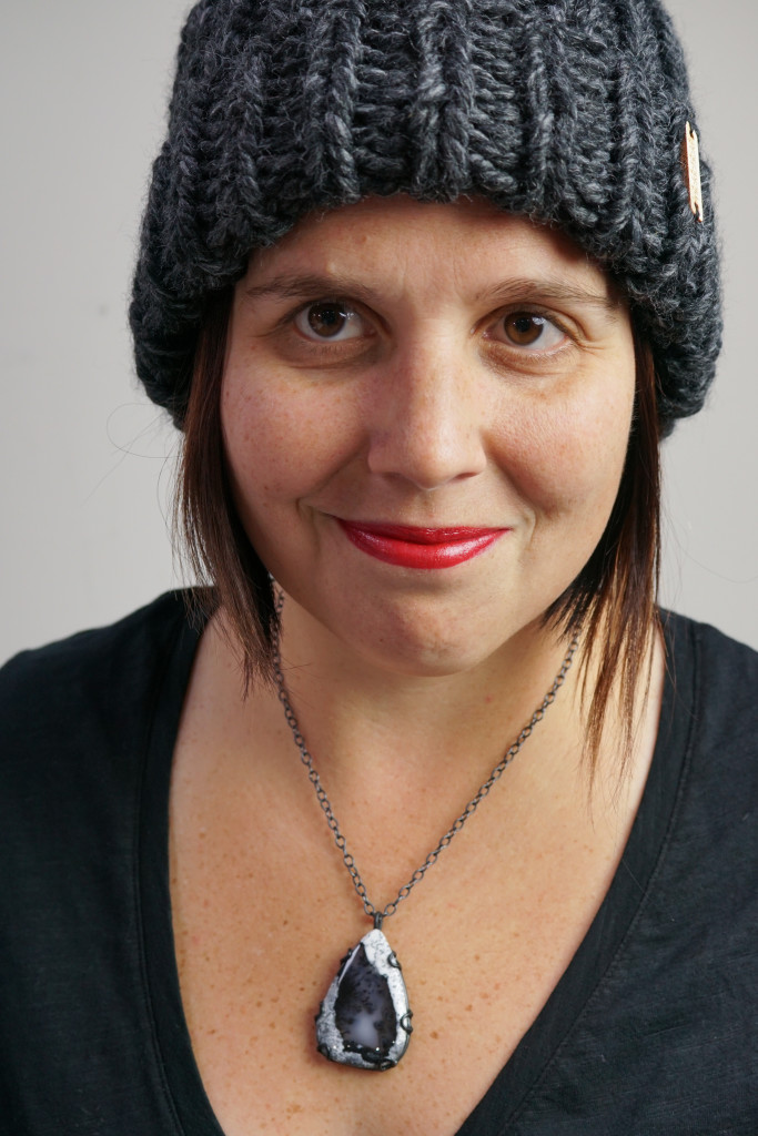 winter style: puffer vest, knit hat, and black gemstone necklace