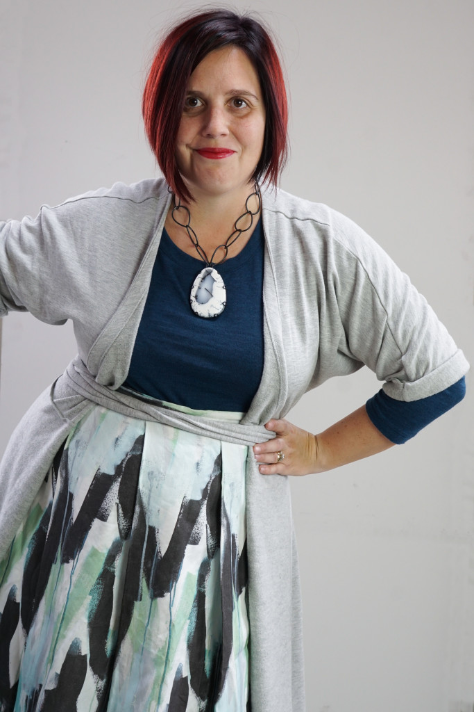 one dress challenge, creative capsule outfit inspiration: wrap dress as a duster over a patterned skirt and teal sweater with a bold gemstone necklace
