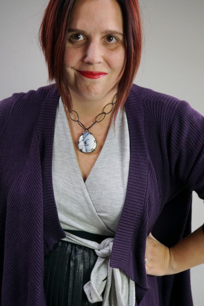one dress thirty ways creative outfit inspiration: grey wrap dress, black metallic skirt, oversized purple cardigan, and chunky gemstone necklace
