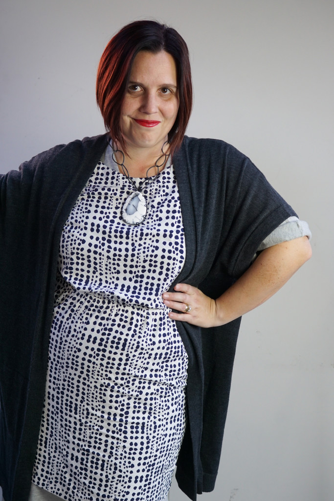 one dress challenge, creative outfit layering: oversized cardigan and patterned dress over wrap dress with chunky gemstone statement necklace