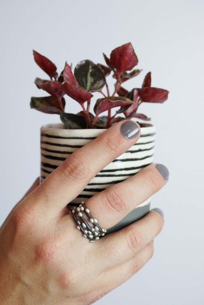 handmade mixed metal stacking rings, striped ceramic cup, and peperomia plant