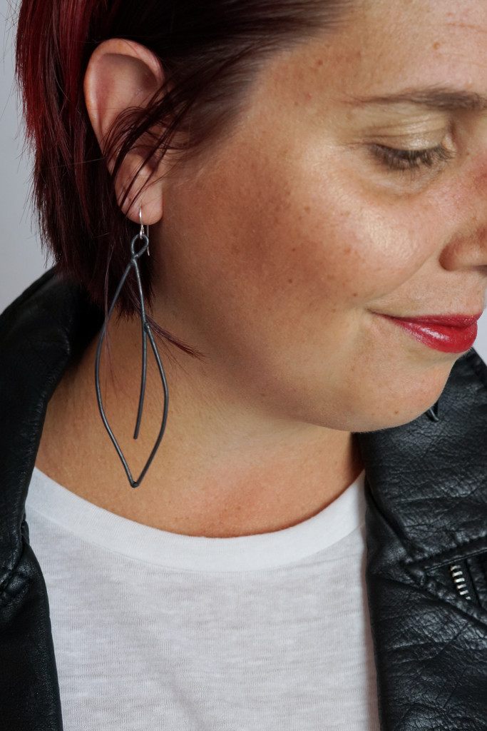 black statement earrings with leather jacket, white t-shirt, and bold red lip