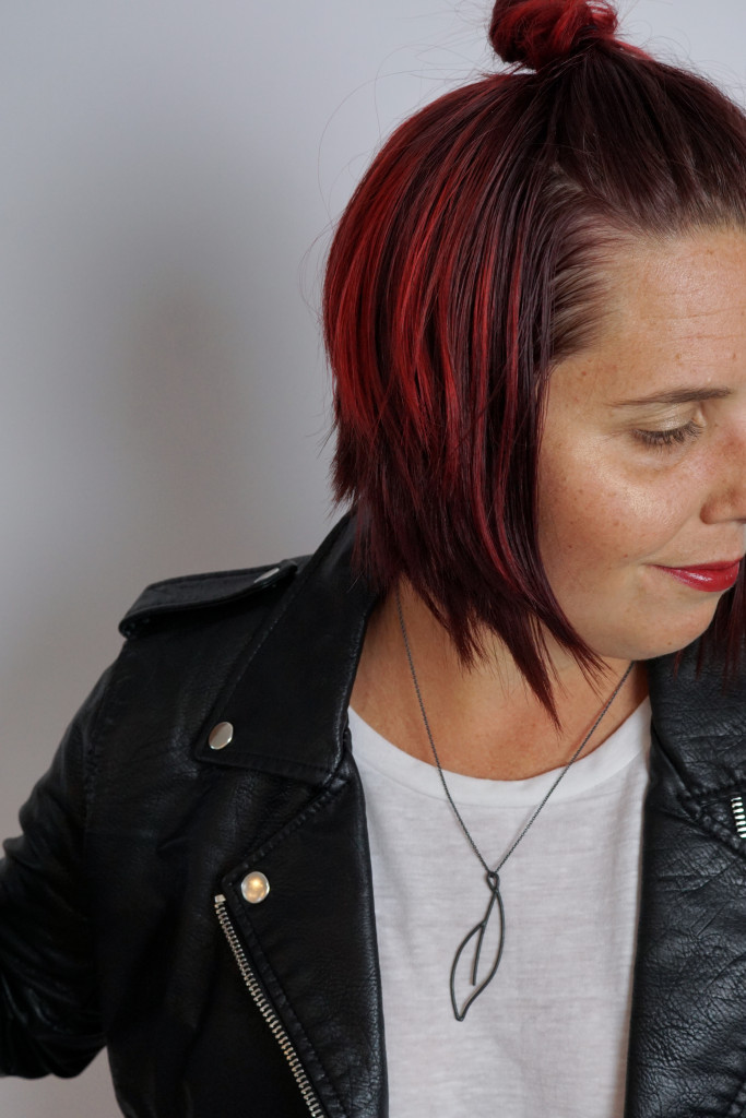 black necklace with a bold lip, white t-shirt, and leather jacket